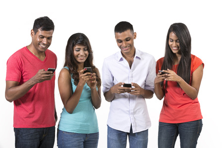 Group of young Indian friends using their smartphones. Happy Asian people using their cell phones. Isolated on white background. photo