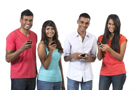 mobile telephones: Group of young Indian friends using their smartphones. Happy Asian people using their cell phones. Isolated on white background.