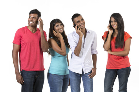 landline phone: Group of young Indian friends using their smartphones. Happy Asian people using their cell phones. Isolated on white background.