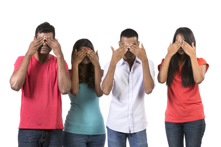 Four Indian people with their hands over their eyes. See no Evil concept. Isolated on white.  Stock Photo