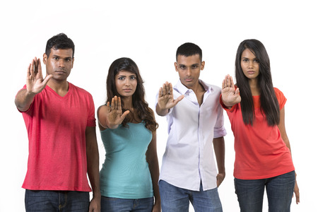 Young group of Indian people with there hands raised in signal to stop. Isolated on white background, Studio shot photo