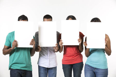 four person: Group of Indian people with a banner ad. Isolated on white background. Stock Photo