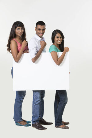 Group of Indian people with a banner ad. Isolated on white background. photo