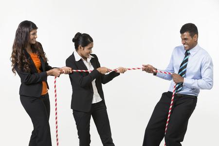 tug o war: Tres hombres de negocios indios jugando tira y afloja. Aislado en el fondo blanco