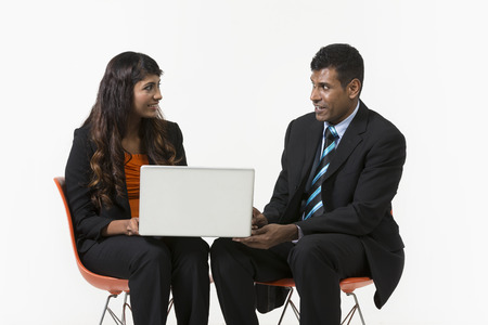 Two Indian Business People sitting down having a meeting using a laptop. Indian man and woman business partners. isolated on a white background. photo