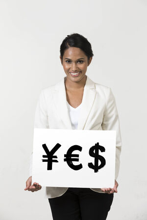 Indian business woman holding currency symbols saying word YES photo