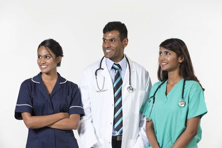 Indian medical team standing on white background looking away. photo