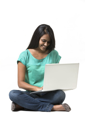 sitted: Indian Woman working on a laptop. Isolated over a white background
