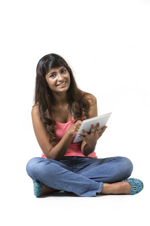 Young woman sitting on floor using a Digital Tablet PC. Isolated on white background. photo