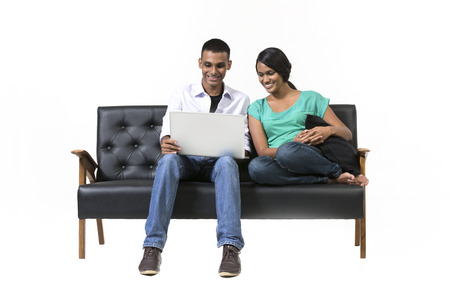 Two Indian friends using a laptop PC on sofa. Indian Man and woman using laptop. Isolated on White Background. photo