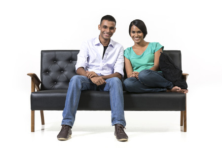 asian woman face: Cheerful young Indian couple sitting on a retro sofa. Isolated on white background.
