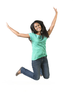 south asians: Excited Indian woman jumping for joy. Beautiful Asian woman jumping isolated on white background. Stock Photo