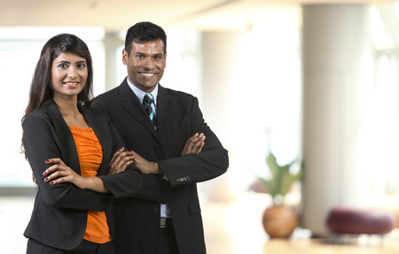 Two Indian Business People standing in an office. Indian man and woman business partners.  Stock Photo