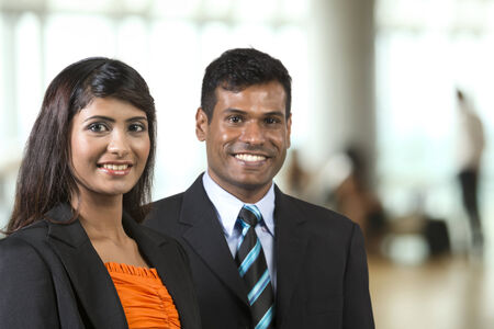 Two Indian Business People standing in an office. Indian man and woman business partners. photo