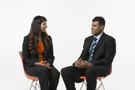 south asian: Two Indian Business People sitting down. Indian man and woman business partners. isolated on a white background.