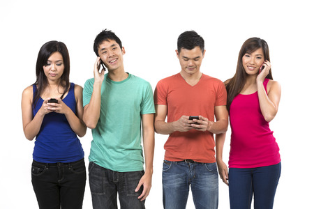 txt: Group of young Chinese friends using their smartphones. Happy Asian people using their cell phones. Isolated on white background.