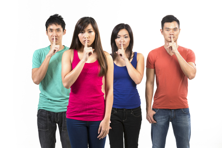 verbal communication: Serious group of Chinese friends with fingers over lips. isolated over white background.