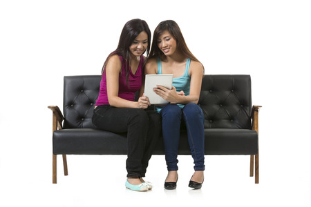 Two Chinese female friends sitting on chair using a Digital Tablet PC. Isolated on white background. photo