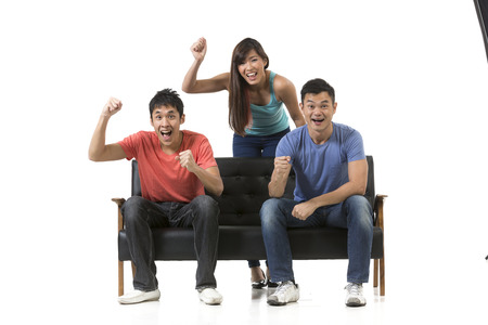 south asian: Happy group of Chinese friends sitting on a sofa watching sport & celebrating. Isolated over white background