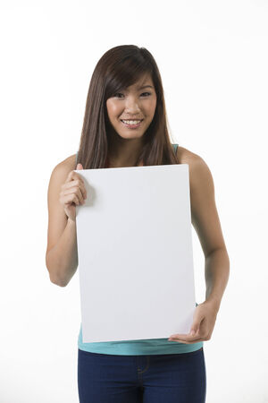 blank billboard: Chinese woman holding up a banner against a white background. Cardboard placard is blank ready for your message.