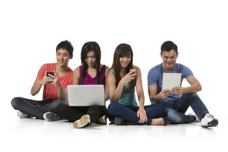 internet movil: Grupo de amigos chinos que utilizan la tecnolog�a moderna. aislado en el fondo blanco.