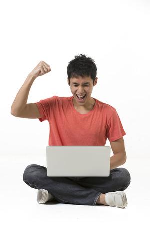 노트북 PC를 사용하는 행복 한 중국 남자. 흰색 배경에 고립입니다.