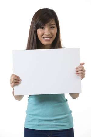 Chinese woman holding up a banner against a white background. Cardboard placard is blank ready for your message. photo