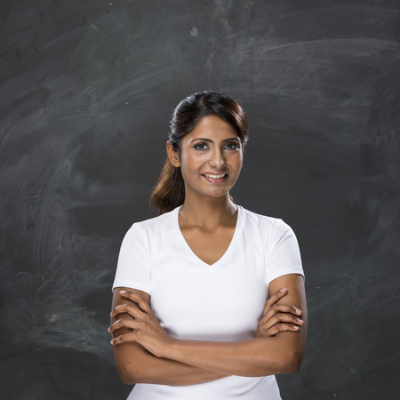 Happy Asian woman standing in front of a dark chalkboard. The chalk board is blank waiting for a message.