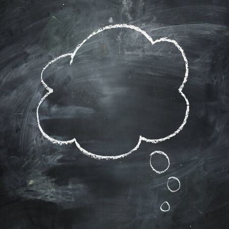 thought bubble: Hand drawn thought bubble on a dark dark chalkboard. Stock Photo