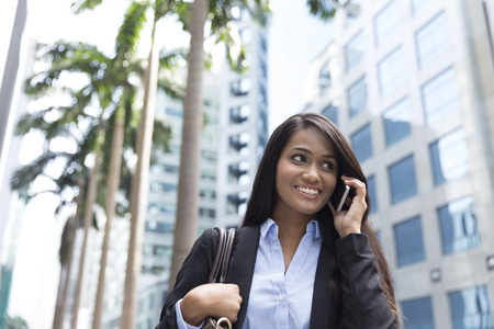 Young Indian businesswoman standing outside using mobile phone photo