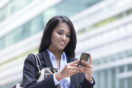 Portrait d'une femme d'affaires indien debout à l'extérieur en utilisant le téléphone mobile pour envoyer un message