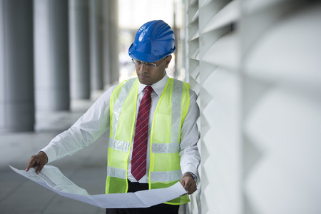 construction plans: Indian engineer at work checking plans on industrial site. Stock Photo