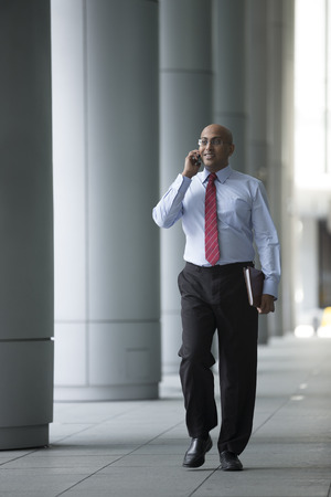 Indian Business man Outside Office using his Mobile Phone. photo