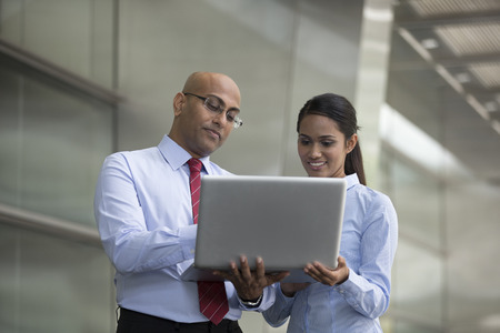 corporate meeting: Indian business Man and woman working together on a laptop outdoors in modern city. Stock Photo