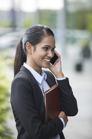 Closeup Portrait of an Indian businesswoman standing outside using mobile phone photo