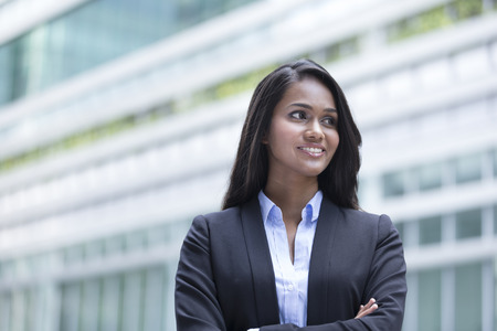 location shot: Young Indian business woman with crossed arms in front of a building. Copyspace to the right