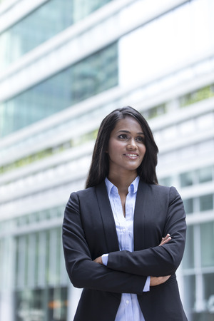location shot: Young Indian business woman with standing outside an office building. Stock Photo