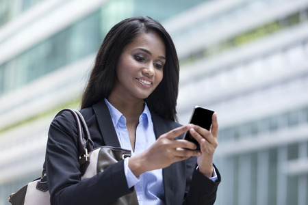 Closeup Portrait of an Indian businesswoman standing outside using mobile phone Stock Photo