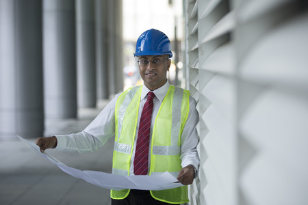 building trade: Indian Architect or engineer at work on a building site. Checking plans against the construction work.