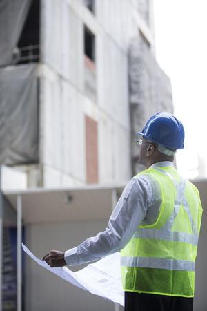 Architecte indien ou ingénieur au travail sur un chantier de construction. Vérification des plans contre les travaux de construction.