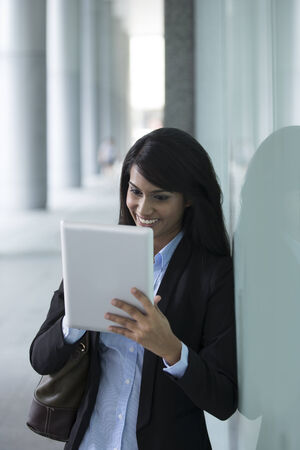 Closeup Portrait of an Indian businesswoman standing outside using a Tablet touchpad photo