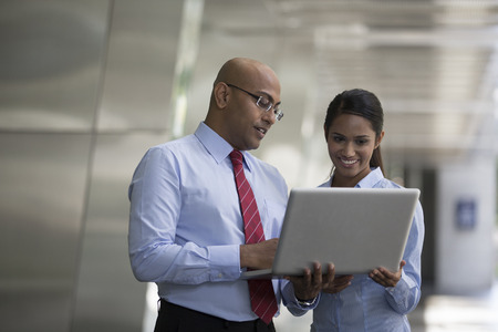 Indian business Man and woman working together on a laptop outdoors in modern city. photo