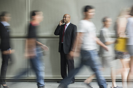 Indian Business man using a Cell Phone with People walking past in a rush. photo