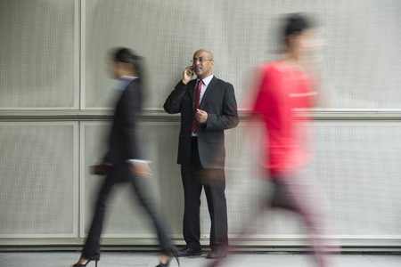 Indian Business man using a Cell Phone with Motion Blurred People walking past. photo
