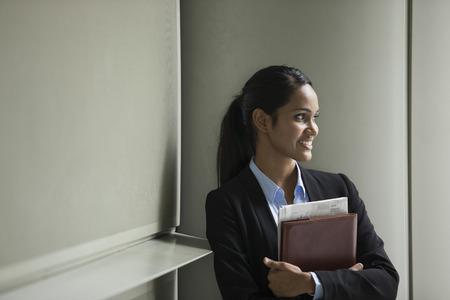 Jeune femme d'affaires indien avec debout à l'extérieur d'un immeuble de bureaux.