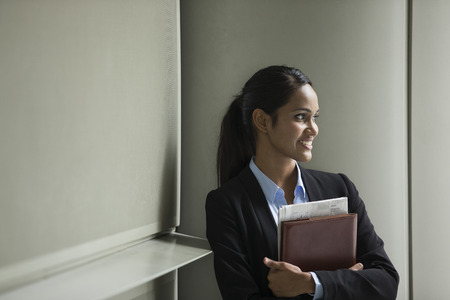Young Indian business woman with standing outside an office building. Stock Photo