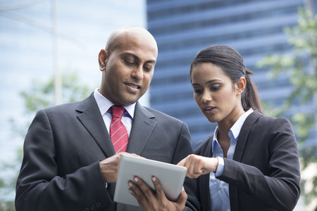 Two Indian business people with digital tablet in a modern urban setting. photo