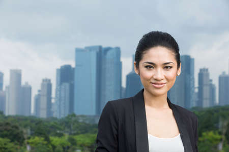 A portrait of a happy Chinese business woman with cityscape in the background. Looking at camera. photo