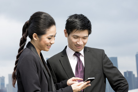 Two Chinese business people standing looking at smart mobile phone. Urban cityskyline in background. photo