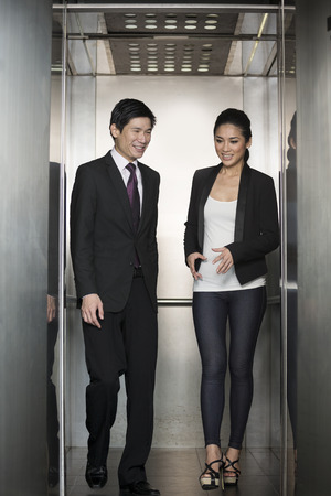 Two happy Chinese business colleagues walking out of an  elevator in a modern office building.